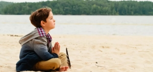 LittleBoyMeditatingAloneOnBeach-850x400